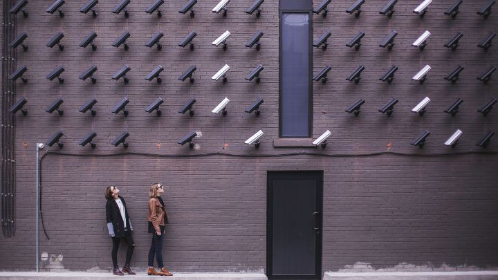 A young couple standing next to a wall, with dozens of security cameras watching them.